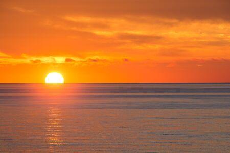 The setting sun over the calm sea