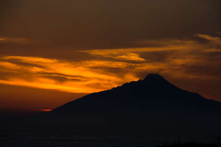 Silhouette of mountains on the sea with the setting sun