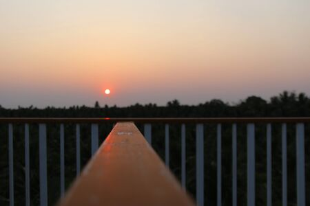 Watch the coconut groves at sunset and the line of sight at the iron fence.