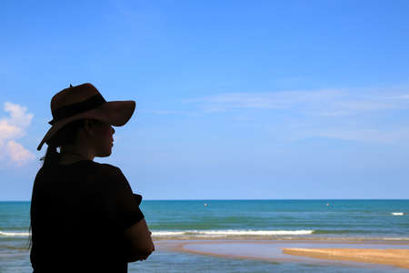 A woman in a wide-brimmed hat stands with her arms folded. Enjoy the nature of the sea and clear sky.