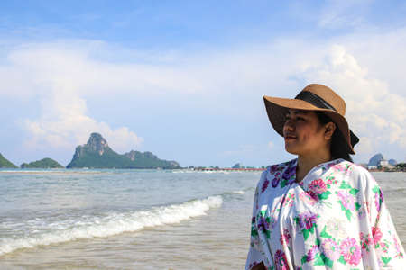 The girl smiled relaxedly while enjoying nature on the beach. On a short vacation