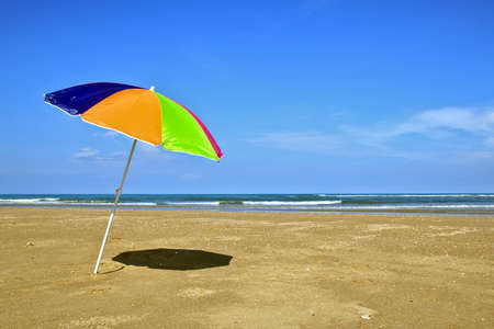 Colorful umbrellas set in the sand with clear skies and empty sea. Without people, without tourists