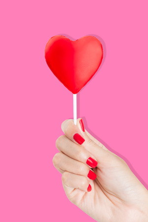 red pink: Woman hand with red nails holding heart Lollipop, on a white background.