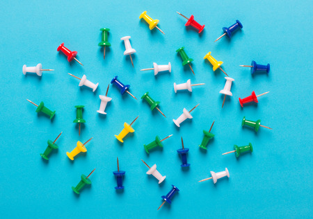 Colorful collection of Push pins in Grouping on blue background. Stock Photo