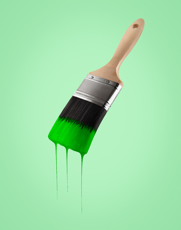 gree: Paintbrush loaded with green color dripping off the bristles, on gree background. Stock Photo