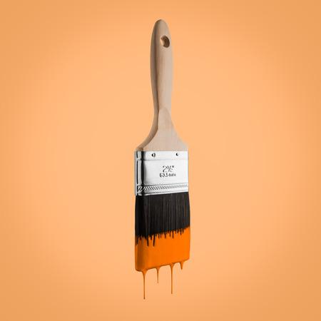 Pinceau chargé de couleur orange qui goutte les poils. Sur fond orange.