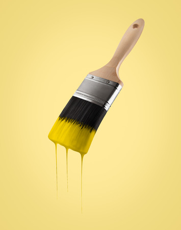 Paintbrush loaded with yellow color dripping off the bristles, on yellow background.