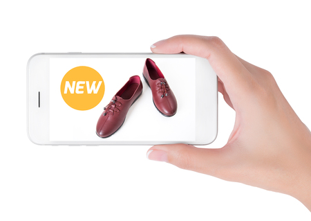 boxing day: woman using smart phone searching new trendy leather shoes fashion information, View of profile with yellow tag and red leather shoes. Fashion and accessories concept, isolated white background. Stock Photo
