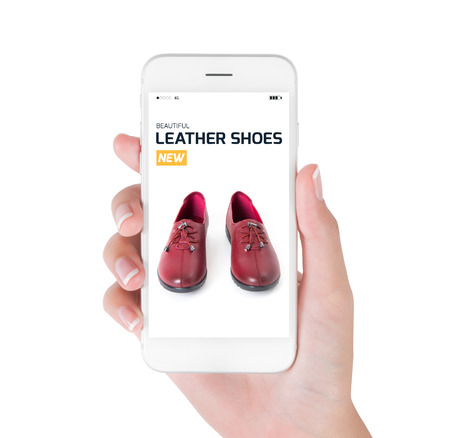 loafer: woman using smart phone searching new trendy leather shoes fashion information, View of profile with yellow tag and red leather shoes. Fashion and accessories concept, isolated white background. Stock Photo