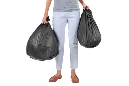 Asian housewife holding garbage bags, isolated on white background. Stock Photo