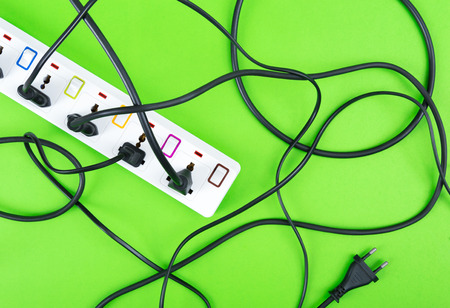 Maximum electrical cords connected electrical power strip or extension block  with messy wires, top view on colorful background, messy electric equipment flat lay concept.
