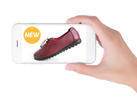 woman using smart phone searching new trendy leather shoes fashion information, View of profile with yellow tag and red leather shoes. Fashion and accessories concept, isolated white background. Stock Photo