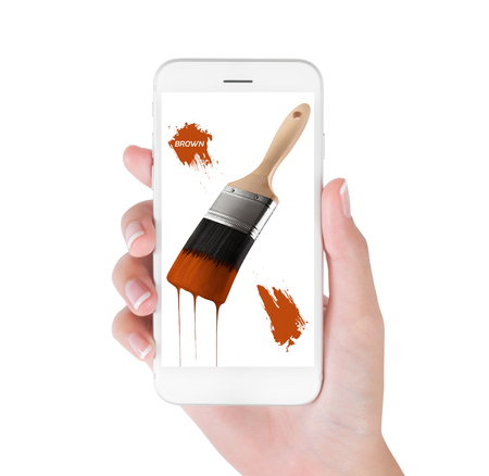 Woman using smart phone searching paintbrush loaded brown color dripping off bristles. Art and Design concept, isolated white background. Stock Photo