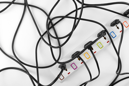 Maximum electrical cords plugs connected electrical power strip or extension block with messy wires, top view on white background, messy electric equipment flat lay concept.