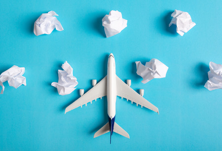 Airplane model flying among paper clouds, Traveling concept