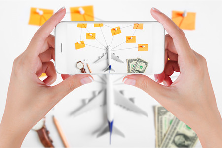 Woman hand using smart phone taking photo for preparation traveling network with push pin, pencil, watch, money, dollar, string, paper noted.  Travel concepts, Ambient blurry background. Stock Photo