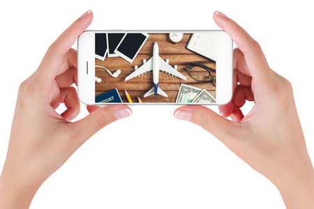 Woman hand using smart phone searching Preparation traveling with pencil, money, passport, airplane, watch, noted book, eyeglasses, earphone and photo frame on vintage wooden. Travel concepts.