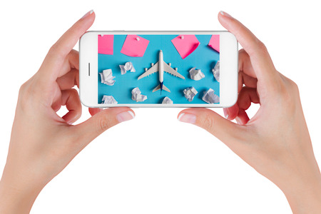 Woman hand using smart phone searching Preparation for Traveling with Airplane model flying among paper clouds and pink paper noted. Travel concepts, Isolated on white background.