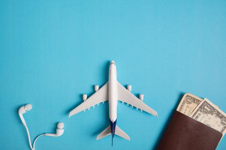コンセプト、飛行機、お金、パスポート、イヤホン、コピー スペースと青色の背景に、本旅行の準備。 写真素材