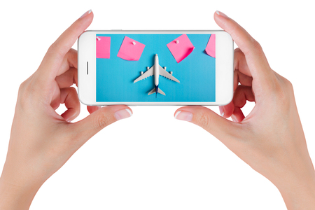 Woman hand using smart phone searching Preparation for Traveling with Blank paper noted and airplane. Travel concepts, Isolated on white background. Stock Photo