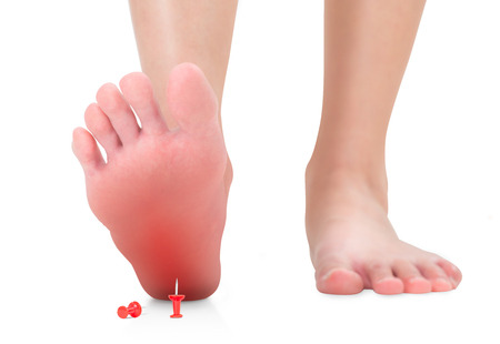 front view of woman's feet stepping on the red push pin, unforeseen concept, red high lighted Isolated on white background.