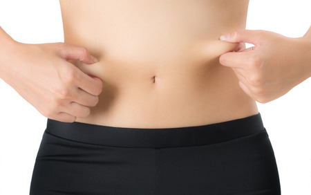 pinches: woman pinches fat on the belly, Isolated on white background. Stock Photo