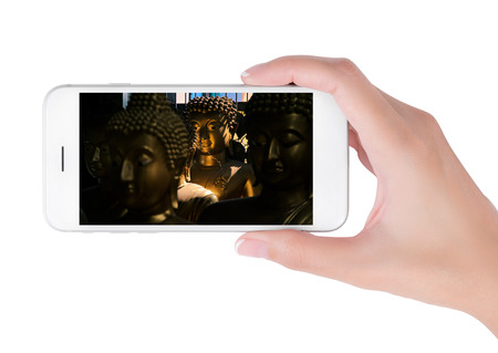 Woman using her smart phone for searching the smiling golden buddha in shadow. Traveling concept, isolated on white background.