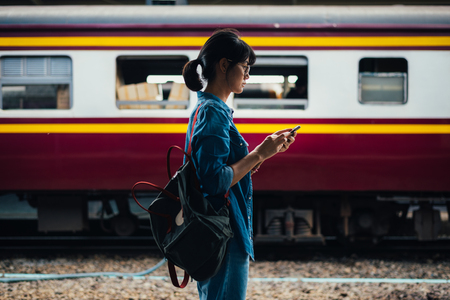 Asian woman traveler used smart phone while wait and check train schedule on the platform of the railway station - travel and transportation concept