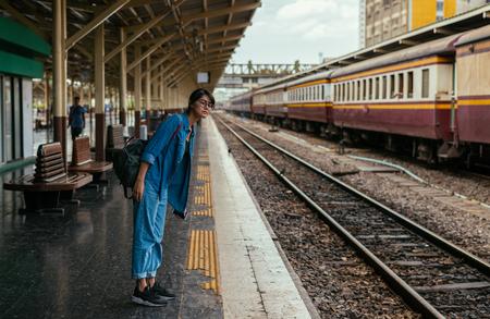 Asian woman traveler waiting train on the platform of the railway station- travel and transportation concept Reklamní fotografie