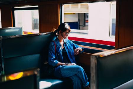 Asiatische Reisende sitzt auf einem Zugsitz und schaut auf eine Uhr für den Wartezug, der den Bahnhof des Bahnhofs verlässt - Reise- und Transportkonzept