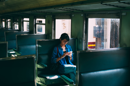 Asiatische Reisende sitzt auf dem Zugsitz und benutzt das Smartphone, während der Zug den Bahnhof des Bahnhofs verlässt - Reise- und Transportkonzept