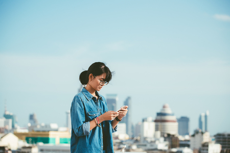 Asian woman used smart phone reads and text message on her smart phone in the city scene background with copy space Banco de Imagens