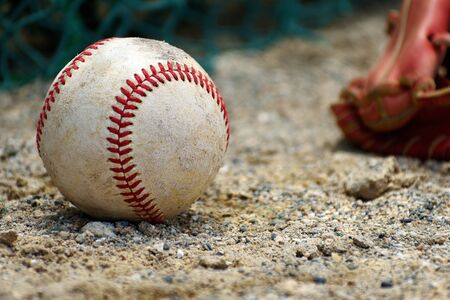 Baseball hard ball and gloves placed on the soil (close-up)