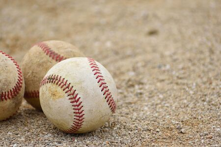Three baseball balls rolling on the soil