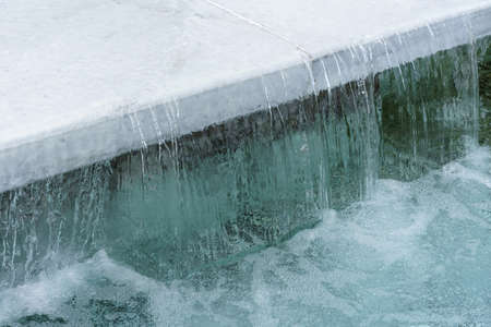 Waterfall from the clear water in the city fountain. Clear water and white granite slab.