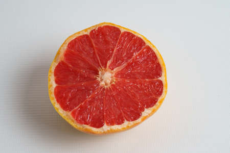 Half a ripe grapefruit on a white plate. Closeup. View from above