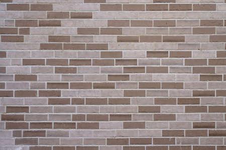 A fragment of a brick wall made of dark and light brown bricks. Papal horizontal sutures.