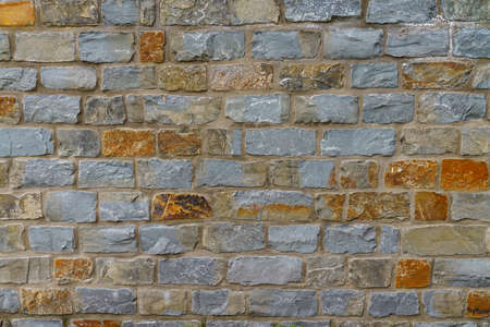 A fragment of a stone wall made of hewn stone. Close up. Stock Photo