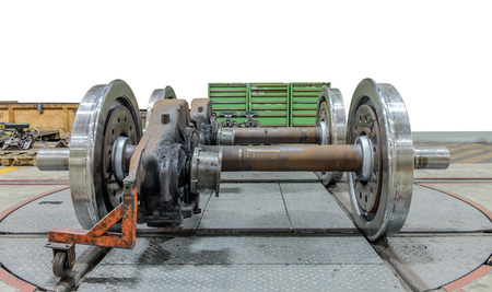 axle: Spare railway wheels on the axle in a repair workshop Stock Photo