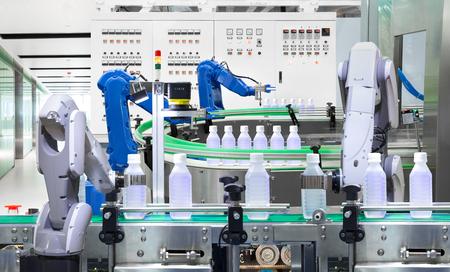 Robotachtige het waterflessen van de wapenholding op productielijn in fabriek, Industrie 4.0 concept Stockfoto