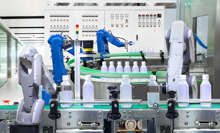 Robotic arm holding water bottles on production line in factory, Industry 4.0 concept