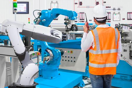 Inżynier utrzymania ruchu steruje automatycznym robotem ręcznym narzędziem w fabryce produkcji przemysłowej Zdjęcie Seryjne
