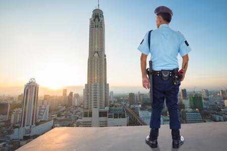 Security guard watching surveillance of metropolis Standard-Bild
