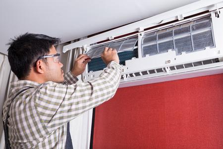 Jonge man elektricien schoonmaken van airconditioning in een klantenhuis