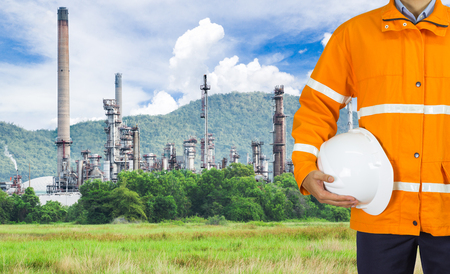 Engineer oil industry wearing safety coat and holding safety helmet in front of oil refinery plant in heavy petrochemical industry estate Standard-Bild