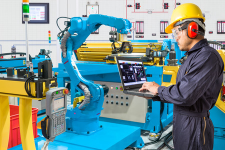 Engineer using laptop computer for control automatic robotic hand machine tool at industrial manufacture factory