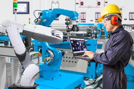 Ingeniero utilizando equipo portátil para el mantenimiento de máquina automática de mano robótica en la fábrica de fabricación industrial Foto de archivo