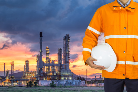 destilacion: Engineer oil industry wearing safety coat and holding safety helmet in front of oil refinery plant in heavy petrochemical industry estate Foto de archivo