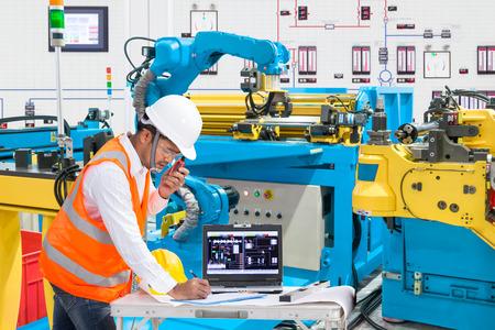 Ingenieur met behulp van laptop computer voor onderhoud automatische robot handmachine gereedschap bij industriële fabricage fabriek Stockfoto