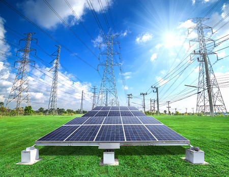 Solar energy panels and high voltage electricity pylon against sunny sky